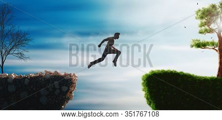 Man Jump Through The Gap Between Hill. Man Jumping Over Cliff On Sunset Background. Business Concept
