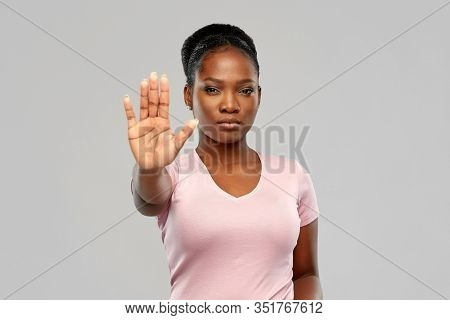 people, prohibition and rejection concept - african american young woman showing stop gesture over grey background