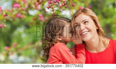 family, motherhood and people concept - happy smiling mother and daughter whispering her secret over cherry blossom background