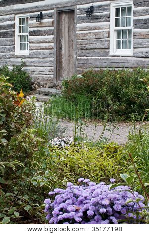 Charming Colonial Garden Showing Front Door Of Rustic Log Cabin