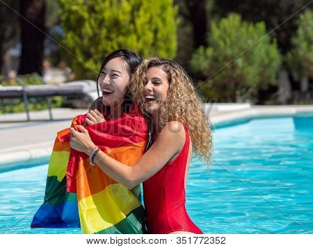 Stock Photo Of Two Girls Of Different Ethnicities In The Water Of A Swimming Pool Embraced While One