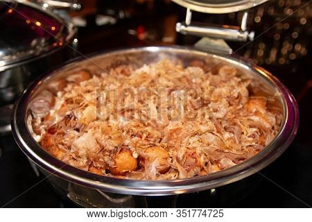 Large Portion Of Japanese Style Takoyaki With Dried Bonito Flakes On Top In A Buffet Tray.