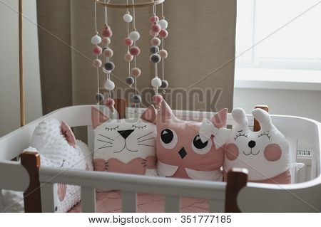 Beautiful Interior Of Baby Room With A Crib. White Crib With Pillows And Pink Blanket In Baby Room.