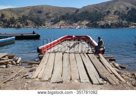 Tiquina, Bolivia - October 22, 2015: Man Sitting On A Wooden Ferry At Lake Titicaca.