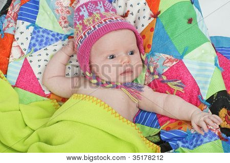 Baby With Colorful Hat And Quilt