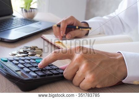 Asian Businessmen Work With Calculators To Calculate Account Information. In The Office, Work Desks