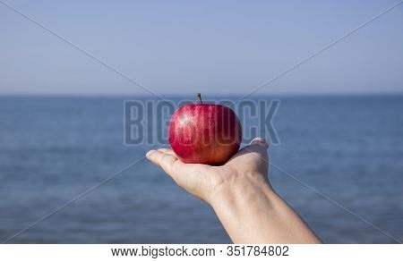 Red Ripe Apple In Hand Against The Sea. Ecotourism And Consumption Of Natural And Organic Fruits.