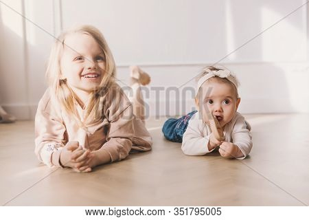 Two Cute Sisters Sitting On Floor And Playing At Home.little Sister Hugging Her Smalest Sister. Todd
