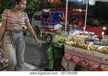 Thailand, Phuket, Patong, February 1, 2020: Asian Thai Woman Walks Past Street Food Banana Pancakes
