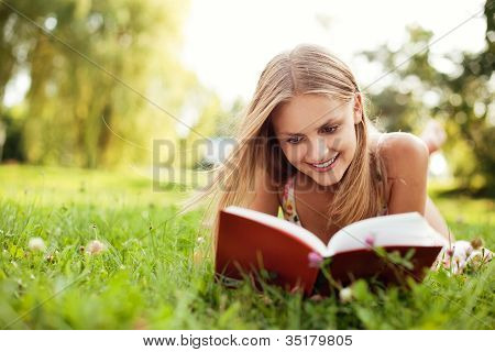Young Woman Reading Book At Park Lying Down On Grass