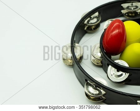Top View Of Black Tambourine With Egg Shakers On A White Background, With Space To The Left Of The I