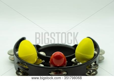 Black Tambourine With Egg Shakers On A White Background. Space Above For Text. Concept Percussion In