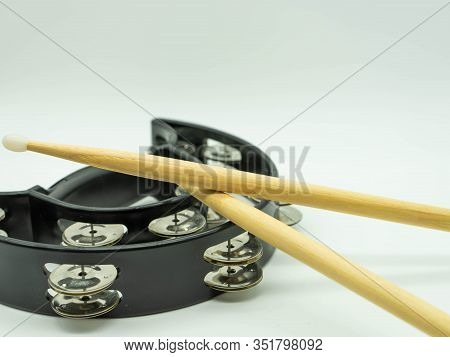 Wooden Drumsticks On A Black Tambourine On A White Background, With Space At The Top Of The Image Fo