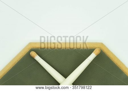 Top View Of Wooden Drumsticks On Practice Pad On A White Background With Space For Text. Musical Ins