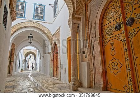Typical Cobbled And Narrow Street With Colorful Doors, Columns And Arcades Inside The Historical Med
