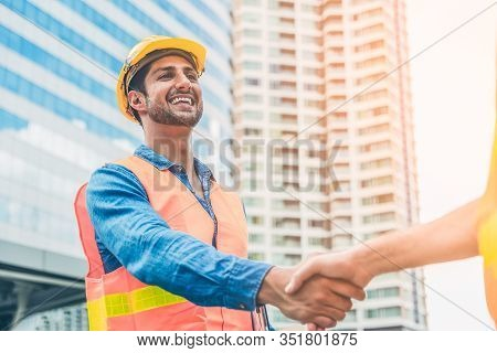 Engineer In Yellow Helmet And Best Greeting With Warm Handshake Manager Visiting Site. Modern Constr