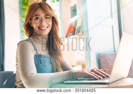 Photo of smiling mature woman in eyeglasses using on laptop while sitting at table in bright room