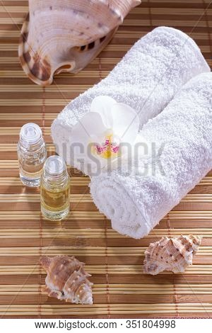 Spa Setting With Towel, Shells, Aromatic Oil, Orchid And Candle.