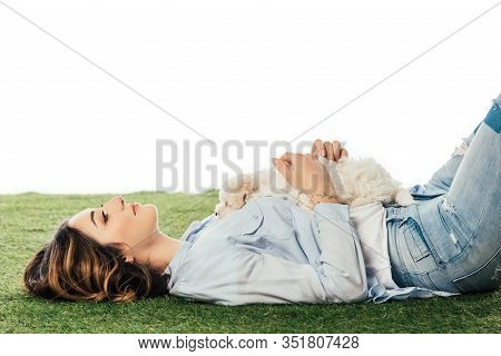 Side View Of Smiling Woman Lying On Grass With Havanese Puppy Isolated On White