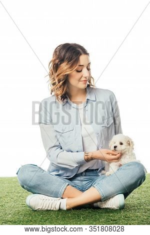 Smiling Woman Stroking Havanese Puppy And Sitting On Grass Isolated On White