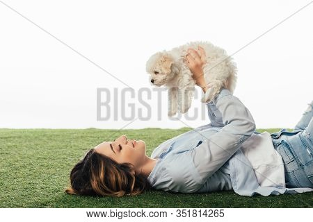Side View Of Smiling Woman Holding Havanese Puppy Isolated On White