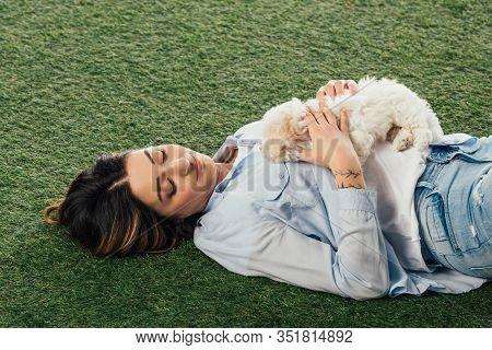 High Angle View Of Woman Holding Havanese Puppy And Lying On Grass