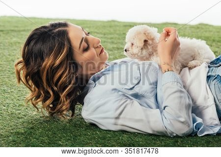 Woman Lying On Grass And Looking At Havanese Puppy Isolated On White