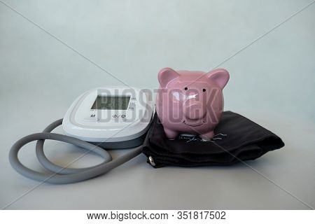 Pink Piggy Bank With Blood Pressure Monitor On White Background, Saving Money For Future Plan And Re