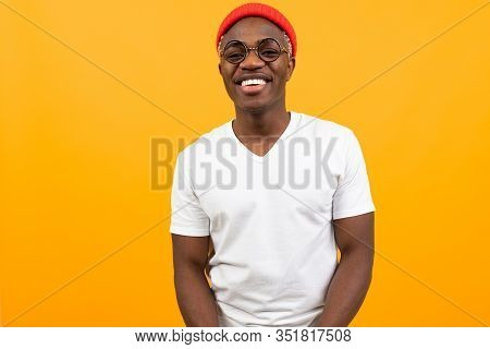 Portrait Of A Stylish Smiling Sexy African Black Man In A White T-shirt With Glasses On A Yellow Bac