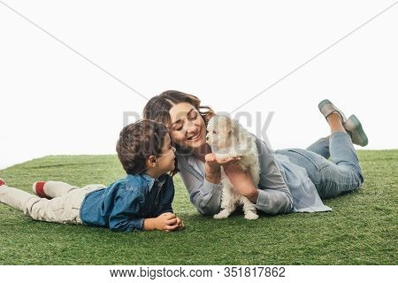 Smiling Mother And Son Looking At Havanese Puppy Isolated On White