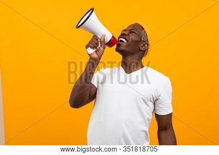 Black African Man Speaks In Megaphone On Isolated Orange Background.