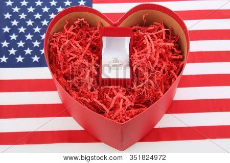 Engagement Ring. Valentines Day Gift. Wedding Ring. Red Heart with an Diamond Engagement Ring. On American Flag. Clipping path. Room for text. Will you marry me? Love is in the air.
