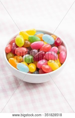 Fruity jellybeans. Tasty colorful jelly beans in bowl on checkered tablecloth.