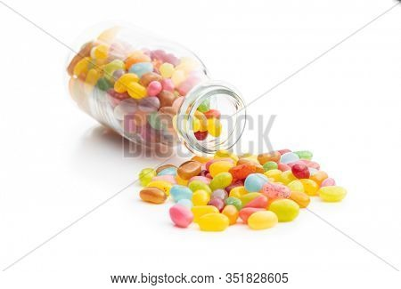Fruity jellybeans. Tasty colorful jelly beans in glass bottle isolated on white background.