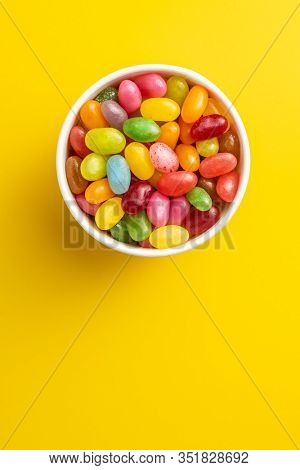 Fruity jellybeans. Tasty colorful jelly beans in bowl on yellow background. Top view.