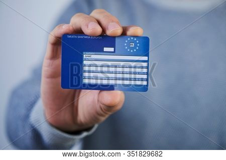 BARCELONA, SPAIN - FEBRUARY 13, 2020: A man, wearing a casual gray pullover, shows a European Health Insurance Card, issued in Spain