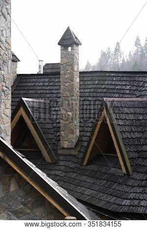 Standing Stone Chimney With Wooden Cap, Roof Windows, Snow Guard And Dormer Window At A Red Tiled Ro