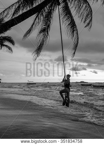 Black And White Photo Of Sexy Young Woman Swinging On The Bungee At The Ocean Beach