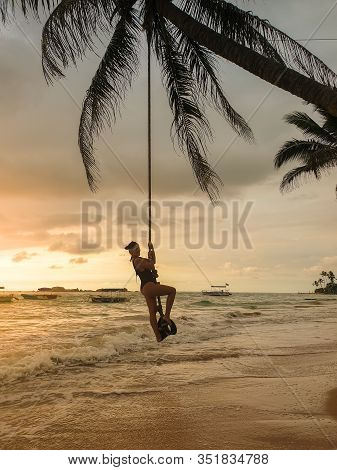 Beautiful Young Woman In Swimsuit Swinging On The Rope Over The Ocean Waves At Sunset
