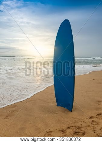 Beautfiul Photo Of Blue Surboard Standing On The Sandy Ocean Beach At Sunset
