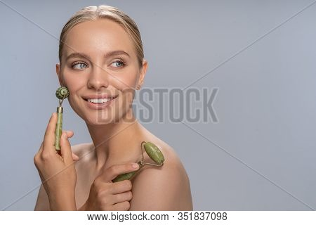 Cheerful Young Woman Doing Face Massage With Jade Roller