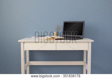Laptop With Black Screen On White Table. Home Office Of A Creative Entrepreneur. Minimalistic Modern