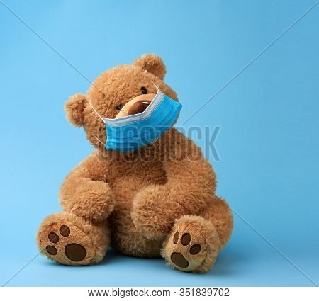 Big Teddy Bear Are Sitting In Blue Medical Masks On A Blue Background, Concept Of Protection From Re