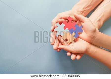 Adult And Chiild Hands Holding Jigsaw Puzzle Shape, Autism Awareness, Autism Spectrum Family Support