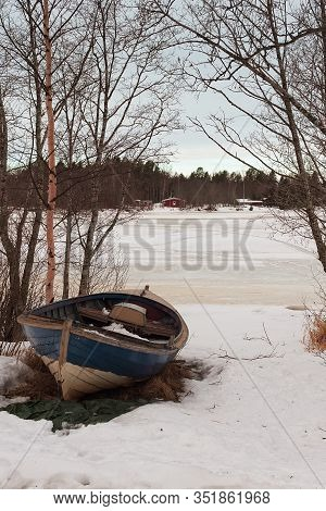 An Old Wooden Fishing Boat Is On The Shore At A Small Village In The Rural Finland. The Sea Is Still