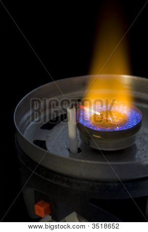flame burner of camping or backpacking stove with a piezoelectric igniter against black background poster