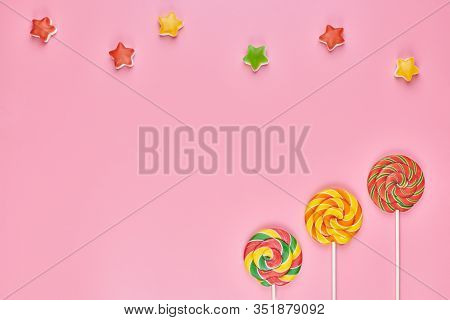 Sweet Lollipops And Candy On Pink Background, Copy Space. Love To Colorful Sweetmeats In Childhood C