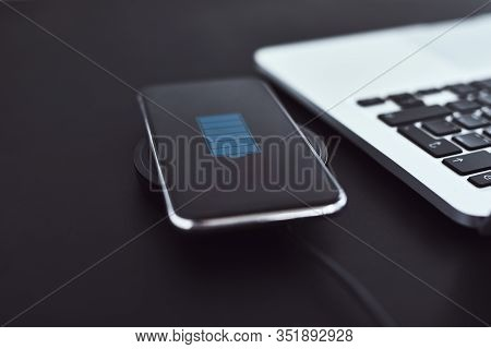 Wireless Charging Of Mobile Phone On Table Next To Laptop
