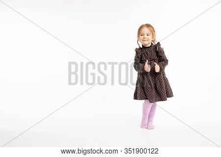 Full Lenght Portrait Of The Pretty Redhead Girl In Dress Holding Thumbs Up Isolated On White Backgro
