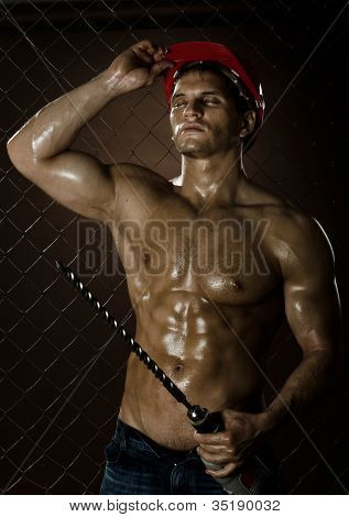 poster of the tired muscular worker driller man hold big perforator in hand vertical photo